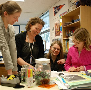 School principal and staff members working together in a classroom