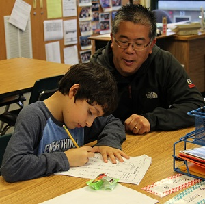 A community volunteer works with an elementary school student
