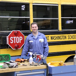 A bus mechanic with tools and supplies in front of a school bus