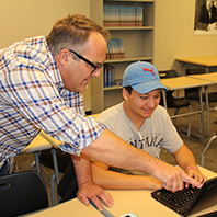 A male teacher with glasses and a male student wearing a hat work together on a laptop.